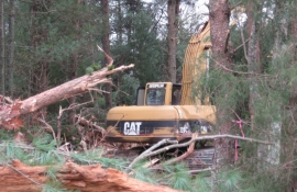 Greg Hutchens on the excavator clearing a fence line and barn site